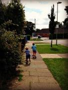 Boys scooting parkwards